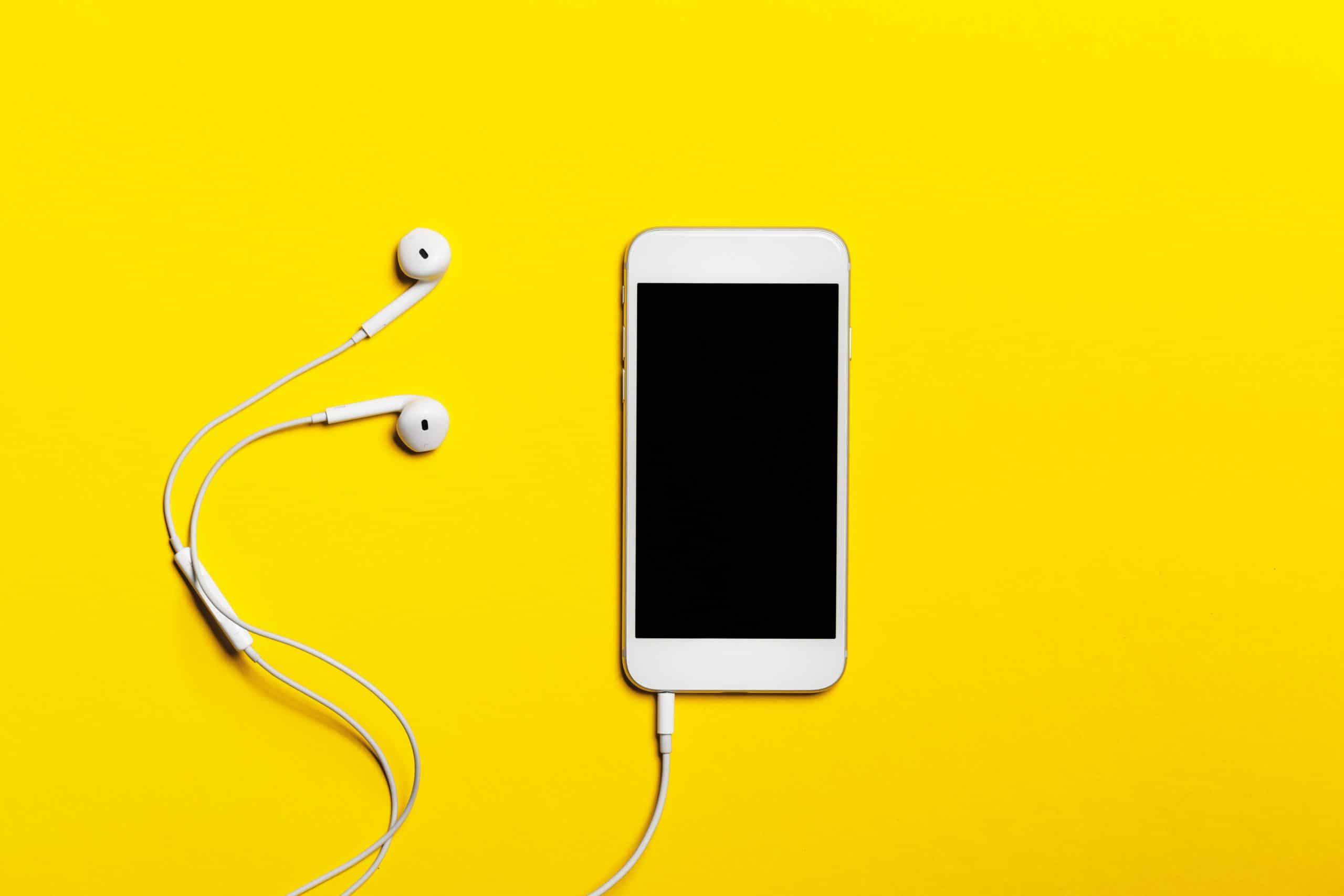 Handy mit Headsets auf gelben Hintergrund